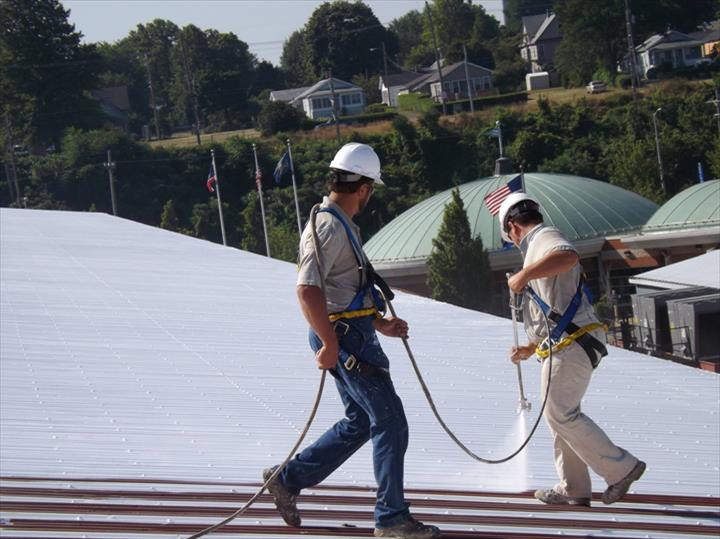 contractors working on silicone roof coating